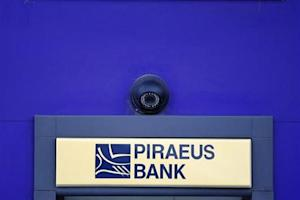 A surveillance camera is seen over the logo of Piraeus Bank on an ATM machine outside one of its branches in Bucharest