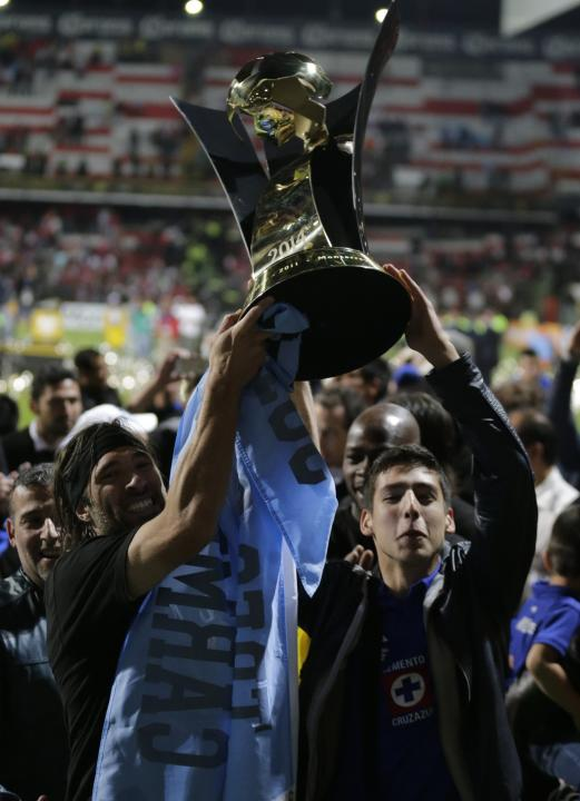 Pavone of Cruz Azul holds the trophy with a teammate after they won their CONCACAF Champions Cup final soccer match against Toluca in Toluca