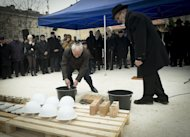 Leader of the Alliance of Hungarian Jewish Faith Communes Gusztav Zoltai (L) and Rabbi Andras Kerenyi place the foundation stone of a new synagogue in the Csepel neighbourhood of Budapest on January 27, 2013. The construction of Budapest's first synagogue in 80 years began Sunday
