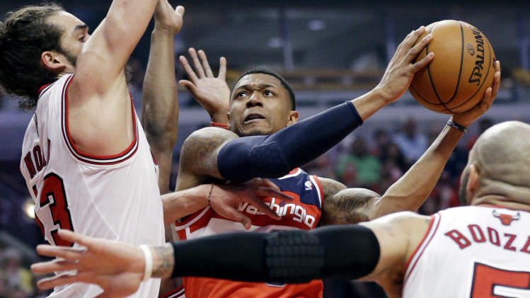 Washington Wizards guard Bradley Beal (3), center, drives to the basket against Chicago Bulls center Joakim Noah, left, and forward Carlos Boozer (5) during the first half in Game 1 of an opening-round NBA basketball playoff series in Chicago, Sunday, April 20, 2014