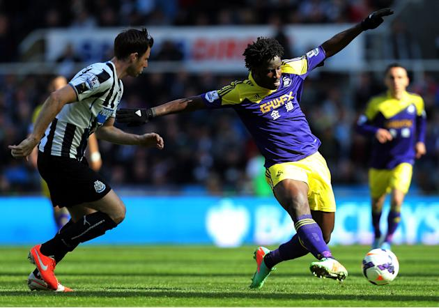 Swansea City's Wilfried Bony, right, vies for the ball with Newcastle United's Mike Williamson, left, during their English Premier League soccer match at St James' Park, Newcastle, England