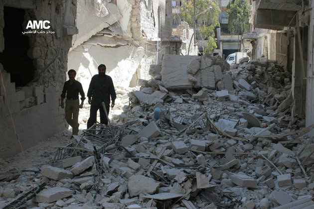 This photo provided by the anti-government activist group Aleppo Media Center (AMC), which has been authenticated based on its contents and other AP reporting, shows Syrian men walk through the rubble of houses that were destroyed by Syrian government forces air strikes in Aleppo, Syria, Monday, April 21, 2014. Syria will hold presidential elections on June 3, the country's parliament speaker announced Monday, a vote President Bashar Assad is likely to win, as the country enters its fourth year of war. (AP Photo/Aleppo Media Center AMC)
