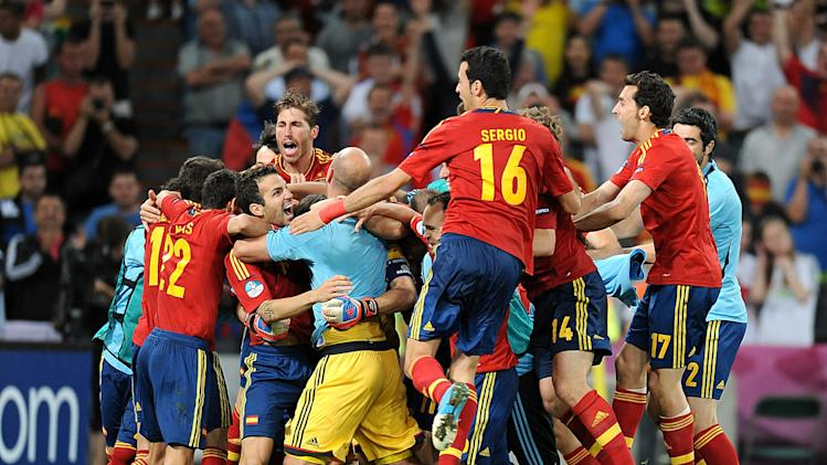 Cesc Fabregas (third left) is mobbed by his Spain team-mates after netting the decisive penalty