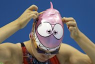 In this July 27, 2012, photo, Jennet Saryyeva of Turkmenistan puts on her goggles during a practice session at the Aquatics Centre in the Olympic Park ahead of the 2012 Summer Olympics in London. Jennet Saryyeva of Turkmenistan was nearly lapped in a preliminary swimming heat_ but for athletes from the world's smallest countries, or those suffering through conflict and turmoil, the Olympics are not about winning, but there is victory and honor in just showing up. (AP Photo/Daniel Ochoa De Olza)