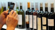 A visitor takes pictures of various bottles of red and white wine with his smartphone. From iPads in vineyards to virtual tastings on Twitter, the tradition-steeped US wine industry is increasingly turning to Internet Age innovations to improve vintages and profits