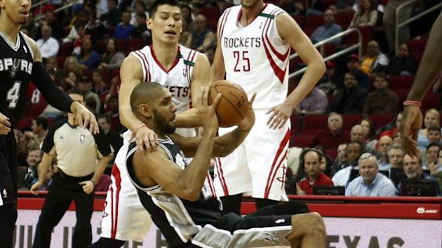 Houston Rockets guard Jeremy Lin and San Antonio Spurs forward Tim Duncan wrestle for control of the ball
