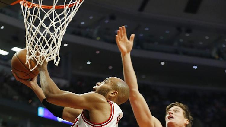 Chicago Bulls forward Taj Gibson, left, goes to the basket in front of Detroit Pistons forward Jonas Jerebko, right, during the first half of an NBA basketball game in Chicago, Saturday, Dec. 7, 2013