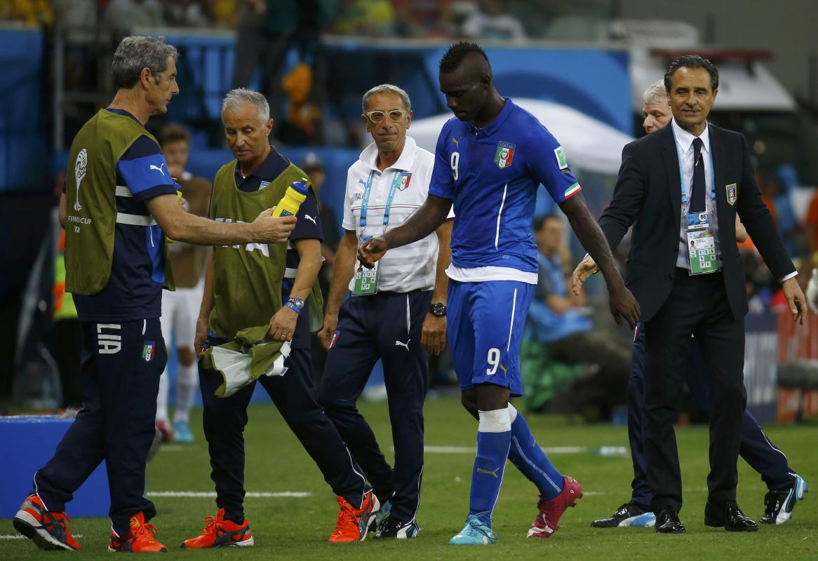 Italy's Mario Balotelli walks past coach Cesare Prandelli during World Cup soccer match between England and Italy in Manaus