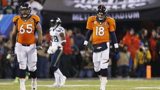 Denver Broncos quarterback Peyton Manning (18) walks with teammate Louis Vasquez after a play against the Seattle Seahawks during the second quarter i...