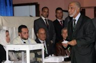 Abdelaziz Belkhadem (R), secretary general of the National Liberation Front (FLN), casts his vote as the FLN held a vote of confidence over Belkhadem's position, in Algiers on January 31, 2013. The central committee of Algeria's ruling party relieved its chief Belkhadem of his duties, an AFP journalist reported.