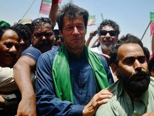 Pakistani politician Imran Khan is surrounded by his supporters during a campaign rally in Karachi on May 7, 2013