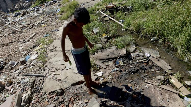 A boy dips his toes in a dirty stream in Metro slum near Maracana stadium in Rio de Janeiro