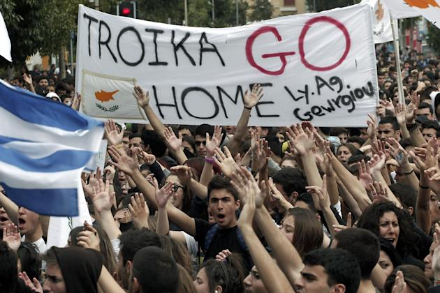 Cypriot students shout slogans near the presidential palace in capital Nicosia, on Tuesday, March 26, 2013. Banks across Cyprus remain firmly padlocked Tuesday after financial authorities extended the