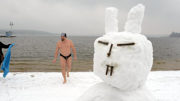 A swimmer gets  out of the water next to a snowman with bunny ears at the snow covered beach of  Strandbad  Lake Wannsee lido  in Berlin, Germany,  Good Friday March 29, 2013.  Bathing season at the lido traditionally starts on Good Friday. '(AP Photo/dpa, Rainer Jensen)