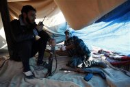 Free Syrian Army fighters rest as one of them uses a talkie-walkie near the the Kwers military airport, where forces loyal to Syria's President Bashar al-Assad are based, in Aleppo September 9, 2013. REUTERS/Loubna Mrie