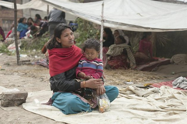 KAT109. Kathmandu (Nepal), 26/04/2015.- A young woman holds a child as local people sit under a makeshift tent roof in the Bhaktapur area of Kathmandu...