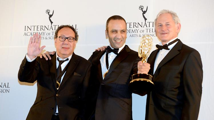 "Producer Claude Chelli, left, and writer Abdul Raouf Dafri, center, celebrate winning an International Emmy for Drama Series for ""Braquo"" with presenter Victor Garber at the 40th International Emmy Awards,  Monday, Nov. 19, 2012 in New York.  (AP Photo/Henny Ray Abrams)"
