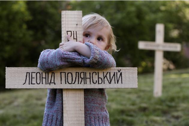 A child embraces one of the 107 wooden crosses, which honour victims of recent protests in Ukraine in Prague