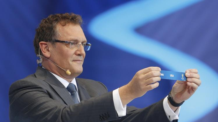 "Valcke holds up the slip showing ""United States"" during the draw for the 2014 World Cup in Sao Joao da Mata"