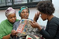 "Relatives look at the newspaper that published photos of taxi driver Mido Macia being dragged. Eight officers have been disarmed and suspended for ""callous and unacceptable behaviour"" and the station commander had been removed from his post pending investigation"
