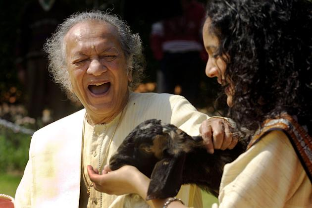 FILE - In this Feb. 25, 2002 file photo, Sitar maestro Pandit Ravi Shankar, left, and his daughter Anoushka Shankar laugh during the shooting of a film endorsing the strengthening of Indian laws again