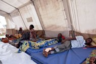 People wounded in blasts at an arms depot in Brazzaville sit in a tent set up near the city's main hospital emergency unit. The death toll from powerful explosions at a Congo munitions dump approached 200 on Tuesday, as international aid began to arrive to help treat over 1,300 wounded and assist 5,000 homeless