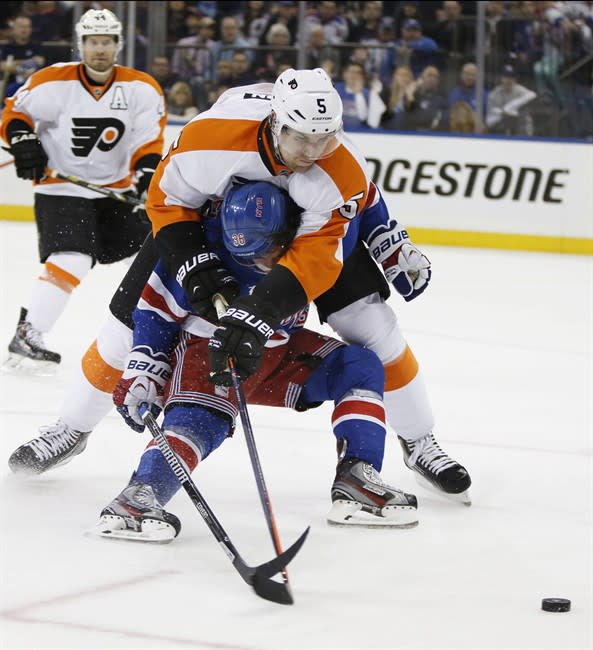 Philadelphia Flyers defenseman Braydon Coburn (5) smothers New York Rangers right wing Mats Zuccarello (36), of Norway, in the second period of Game 2 of the first round of the Stanley Cup hockey play