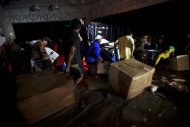 People carry looted goods as they walk through a flooded street in Acapulco September 18, 2013. REUTERS/Jacobo Garcia