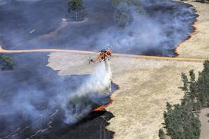 A helicopter dumps water on a bushfire burning in the Grampians bushland in the southeastern Australian state of Victoria