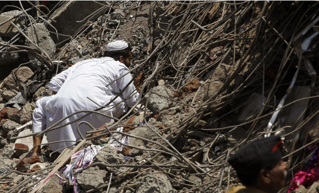 An Indian man looks for survivors in the debris of a building that collapsed on the outskirts of Mumbai, India, Friday, April 5, 2013. The half-finished building that was being constructed illegally i