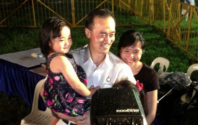 Dr Koh Poh Koon with his two daughters (one hidden by camera) and his wife.