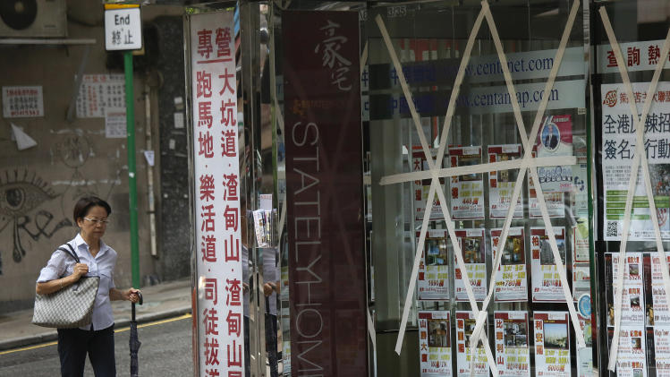 A woman walks past a shop with its glass windows taped to keep from breaking by gust wind in Hong Kong Wednesday, Aug. 14, 2013. Typhoon Utor lashed Hong Kong with wind and rain, closing down the bustling Asian financial center Wednesday before sweeping toward mainland China. (AP Photo/Vincent Yu)