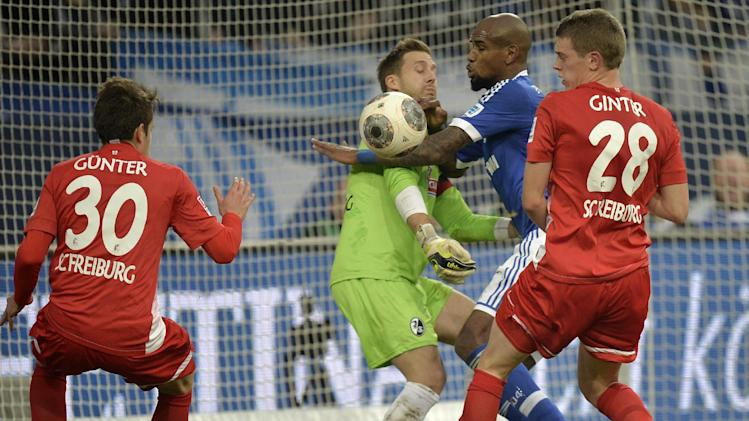 Schalke's Felipe Santana misses to score in front of Freiburg goalkeeper Oliver Baumann during the German Bundesliga soccer match between FC Schalke 04 and SC Freiburg in Gelsenkirchen, Germany, Sunday, Dec. 15, 2013