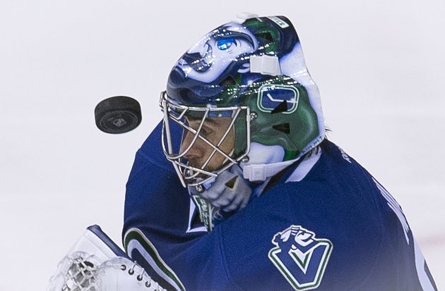 Vancouver Canucks goalie Ryan Miller (30) keeps his eye on the puck during the third period of an NHL hockey game, Saturday, Dec. 13, 2014 in Vancouver, British Columbia. (AP Photo/The Canadian Press, Jonathan Hayward)