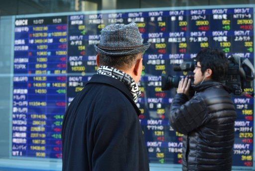 People pass an electronic share price board in Tokyo. Asian markets climbed on Thursday after China released better-than-expected trade data that provide further evidence the world's number two economy has emerged from a drawn-out slumber.