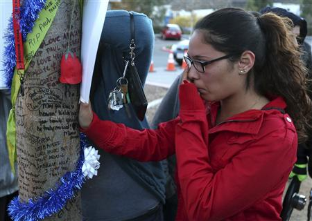 "Krysha Converse wipes a tear reading notes written on a tree during an unofficial memorial event for ""Fast and Furious"" star Paul Walker in Santa Clarita, California December 8, 2013. REUTERS/Jonathan Alcorn"