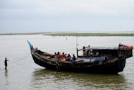 Bangladeshi Border Guards, wading in water, turn back an intercepted boat transporting Rohingya Muslims. Rohingya Muslims from Myanmar living in refugee camps in Bangladesh called for democracy champion Aung San Suu Kyi to speak up for them and help end their persecution