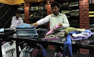 "One of the two Indian owners of the 'Hitler' clothing store, Rajesh Shah (centre), arranges clothing in his shop in Ahmedabad on August 28. The owner of an Indian store called ""Hitler"" said Tuesday he had agreed to drop the Nazi dictator's name and re-brand his shop following protests from the Jewish community and the government"