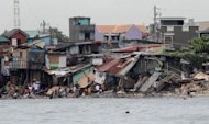Residents salvage housing materials from a Manila Bay community that was destroyed by Typhoon Nesat. Slum dwellers in the Philippine capital rummaged through their flattened homes Thursday as villagers on remote farms battled floods, two days after a monster typhoon killed at least 39 people
