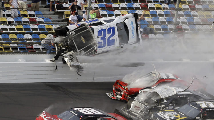 Kyle Larson (32) goes airborne and into the catch fence in a multi-car crash involving Dale Earnhardt Jr. (88), Parker Kilgerman (77), Justin Allgaier (31) and Brian Scott (2) during the final lap of the NASCAR Nationwide Series auto race at Daytona International Speedway, Saturday, Feb. 23, 2013, in Daytona Beach, Fla. (AP Photo/John Raoux)