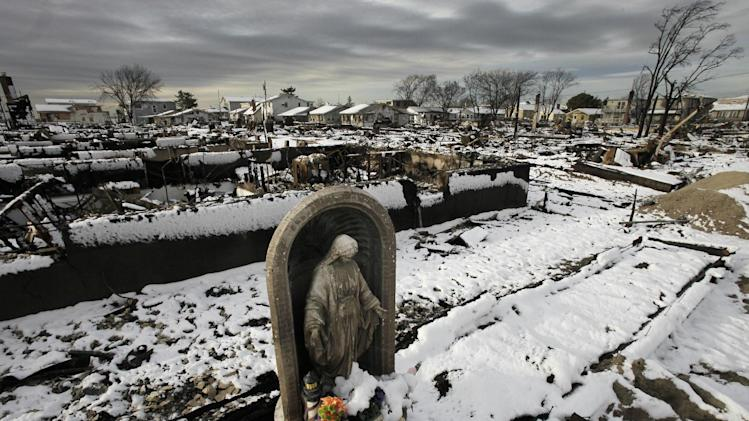 A religious statue stands in the fire-scorched landscape of Breezy Point after a Nor'easter snow, Thursday, Nov. 8, 2012 in New York.  The beachfront neighborhood was devastated during Superstorm Sandy when a fire pushed by the raging winds destroyed many homes.  (AP Photo/Mark Lennihan)