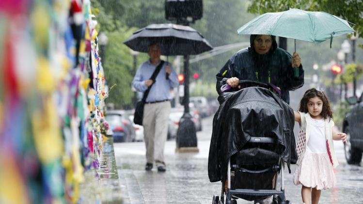 A woman and child walk through heavy rain in Boston, Friday, June 7, 2013. The National Weather Service has issued flood warnings for much of Central and Western Massachusetts as the remnants of tropical storm Andrea move through the region. (AP Photo/Michael Dwyer)