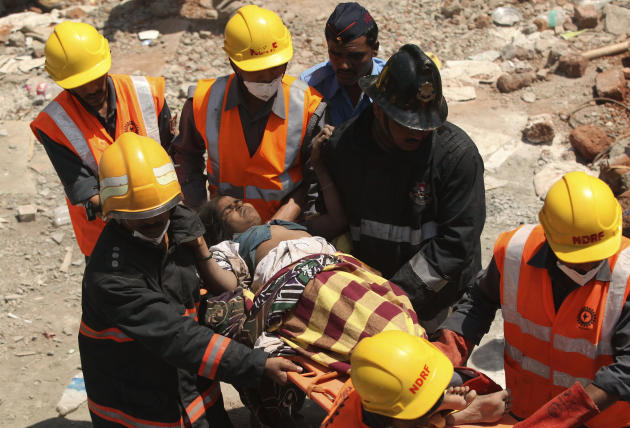 Indian rescue workers help an injured woman after a building collapse on the outskirts of Mumbai, India, Friday, April 5, 2013. The half-finished building that was being constructed illegally in a sub