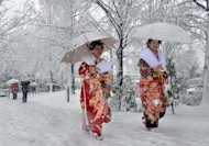 Women dressed in kimonos walk on a snow covered street to a coming-of-age ceremony in Tokyo on January 14, 2013. The winter's first snowfall blanketed the Japanese capital and its environs, paralysing traffic and stranding young people taking part in traditional coming-of-age ceremonies