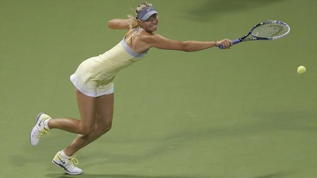 Maria Sharapova of Russia returns the ball to Caroline Garcia of France during their women's match at the Qatar Open tennis tournament in Doha February 12, 2013. REUTERS/Fadi Al-Assaad