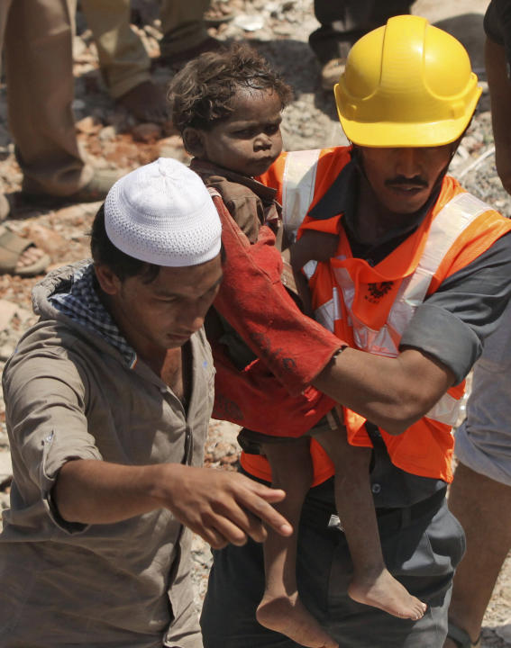 Indian rescue workers carry a young child who survived a building collapse on the outskirts of Mumbai, India, Friday, April 5, 2013. The half-finished building that was being constructed illegally in