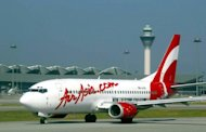 An Air Asia plane prepares for take-off at Kuala Lumpur airport February 8, 2003. Asia's largest low-cost carrier AirAsia announced plans to invest in an airline joint venture with India's giant Tata conglomerate and another investor