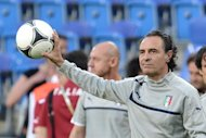 Italian headcoach Cesare Prandelli holds a ball during a training session of the Italian team at the municipal stadium in Poznan on June 17, 2012 on the eve of the Group C match Italy vs Ireland during the Euro 2012 football championships. AFP PHOTO / GIUSEPPE CACACE