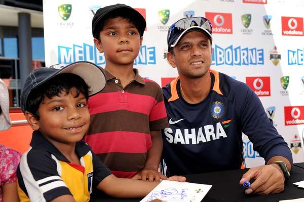 Indian cricket player Rahul Dravid (R) poses with fans as members of the Indian and Australian teams meet the public at an event in Melbourne on December 23, 2011.  Australia and India meet in the fir