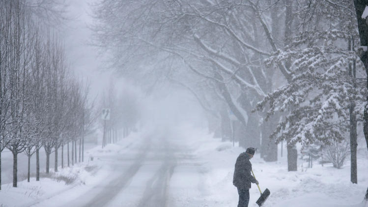 John Baer of Elgin, Ill.  finishes shoveling half of his driveway on Wing Park Ave. during a snow storm in the suburbs of Chicago, Ill. on Tuesday, March 5, 2013. (AP Photo/Daily Herald, Brian Hill)